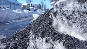 Kuvassa lumikinos, jonka päällä on kadulta pois aurattua hiekotushiekkaa. Vieressä jo lähes sulanut pyörätie.