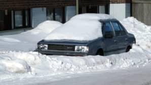Kuvassa lumeen hautautunut auto kadun varrella.