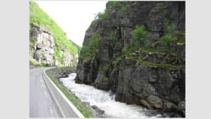 Kvuassa vuorensolassa kulkeva tie, jonka varressa virtaa vuoristopuro.