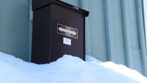 Kuvassa puutalon seinässä oleva postilaatikko. Lumikinos yltää laatikon alareunaan asti.