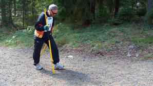 Mies kävelee kahden rautakangen kera metsätiellä