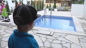 Pieni poika katsoo uima-allasta.