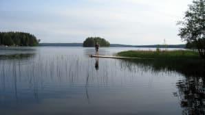 Kalastaja laiturilla järvimaisemassa