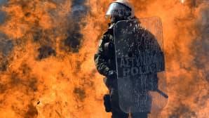 Palopommi räjähtää mellakkapoliisin selän takana mielenosoituksessa.