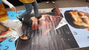 Ihmiset protestoivat YK:n päämajan edustalla New Yorkissa 26. syyskuuta 2012 Iranin presidentin Mahmoud Ahmadinejadin YK:n yleiskokouksessa pitämää puhetta vastaan kävelemällä tämän kuvan päältä.