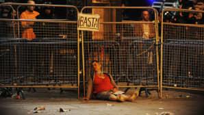 Loukkaantunut nainen nojaa mellakka-aitoihin talouskriisin vaikutuksia vastaan protestoineen mielenosoituksen aikana.
