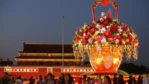 Ihmiset katselevat Kiinan kansallispäivän kunniaksi pystytettyä valtavaa valaistua kukka-asetelmaa Taivaallisen rauhan aukiolla.