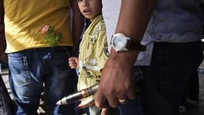 Libyalaispoika pitelee kukkaa ja hänen isänsä isokaliiberisia ammuksia, jotka hän aikoo luovuttaa viranomaisille.