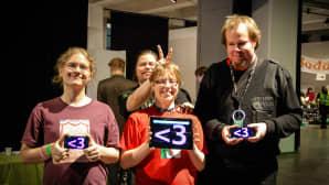 Kolme ihmistä, joiden pitelemien mobiililaitteiden näytöillä on sydän.