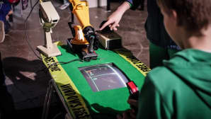 Robottikäsi ja ihminen pelaavat Pongia toisiaan vastaan.