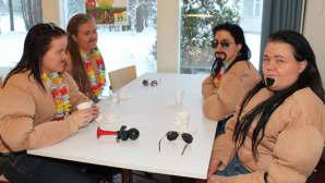 Kuvassa naamiaisasuisia abiturientteja pöydän ääressä istumassa