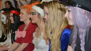 Kuvassa naamiaisasuisia opiskelijoita rivissä istumassa