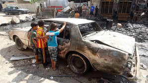 Lapset tutkivat edellisenä päivänä autopommiräjähdyksessä palaneen auton romua.
