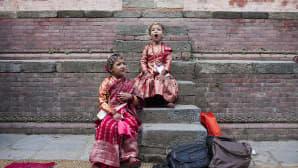 Kaksi perinteisiin asuihin pukeutunutta tyttöä odottaa Kumari Puja -juhlan alkua.