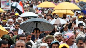 Mielenosoittajia sateessa.