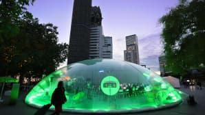 Vihreä, läpinäkyvä teltta öisellä torilla.
