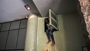 Nainen hyppäämässä ulos katon rajassa olevasta ikkunasta.