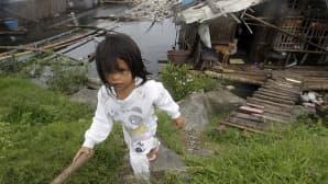 Filippiiniläistyttö kävelee Manilan eteläpuolella sijaitsevan Paranaquen kaupungin rannalle rakennetun hökkelikylän rinteellä.