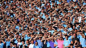 Manchester Cityn kannattajat suojaavat silmiään auringolta paikalliskamppailussa Manchester Unitedia vastaan Etihad-stadionilla.