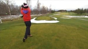 Mies lyö golfkentällä.