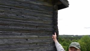 Mies osoittaa luodinreikiä riihen seinässä.
