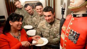 Nainen tarjoilee sotilaille kakkua.