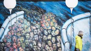 Nainen ohitti Berliiniin muurin sijaintipaikalle pystytetyn installaation.