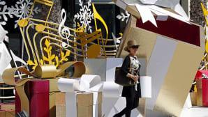 nainen kävelee joulukoristeiden keskellä ostoskeskuksessa