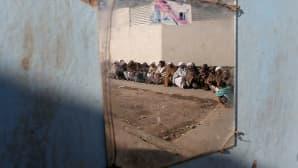 kolmetoista miestä istuu seinänvierellä maassa