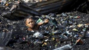 Poika on kaulaansa myöten palaneiden roskien seassa.