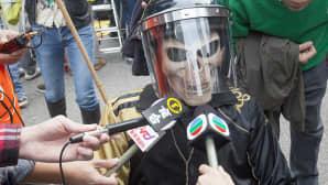 Kypärään ja naamioon pukeutunutta mienosoittajaa haastatellaan.