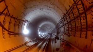 Metrotunneli on rakenteilla Moskovassa. Punaista ja siniharmaata valoa heijastuu tunnelin seinälle.