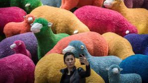 Nainen ottaa itsestään selfien Hongkongilaistavaratalossa lammas-installaation edustalla 18. helmikuuta 2015.