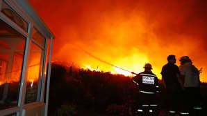 Palomiehet yrittävät estää maastopaloa tuhoamasta vanhusten palvelutaloa.