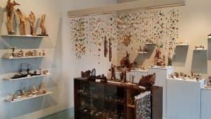 Kuvassa erilaisia esineitä hyllyillä, myös  kattoon on ripustettu eri materiaaleista koottuja taideteoksia