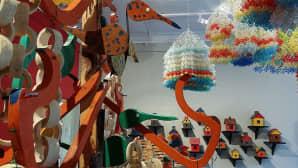 Kuvassa erilaisia lintuihin liittyviä hahmoja , seinällä värikkäitä linnunpönttöjä.