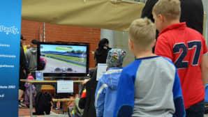 Pojat seuraavat autoilupeliä tv-ruudusta.