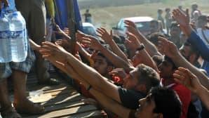 Vapaaehtoiset jakavat vettä siirtolaisille Idomenin kylän lähistöllä pohjois-Kreikassa.