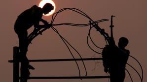 kaksi sähkömiestä asentamassa sähköpylväissä