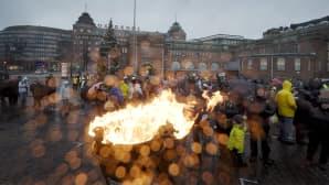 Ihmisiä ja suuressa padassa palava tuli Hakaniemen torilla.