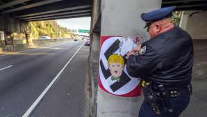 Poliisi poistaa betonipylväästä julistetta joka kuvaa Donald Trumppia keskellä hakaristia.