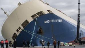 Runsaasti kallistunut laiva satamassa.