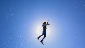 Mies lentää sinistä taivasta vasten.