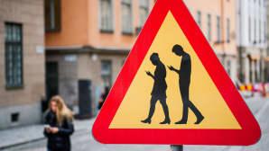 Älypuhelimiin uppoutuneista jalankulkijoista varoittava liikennemerkki Tukholman vanhassa kaupungissa.