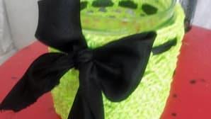 vihreä tuikkupurkin päällinen, jossa musta rusetti