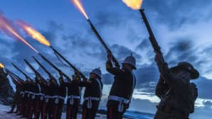 Rivi historiallisesti pukeutuneita sotilaita ampuu ilmaan,