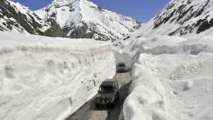 Tiellä jota reunustaa usean metrin lumivallit ajaa kaksi autoa.