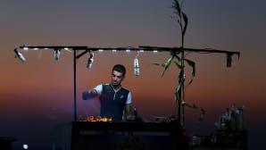 Palestiinalainen mies paistaa maissia rannalla auringonlaskun aikaan, Gazassa.