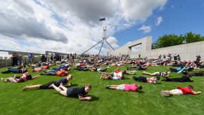 Sadat ihmiset kierivät maassa parlamenttitalon edustalla Canberassa, Australiassa, 17. joulukuuta. Paikallisen miehen innoittamat asukkaat nauttivat nurmikentästä ennen kuin sille rakennetaan ristiriitaisia reaktioita herättänyt turvallisuusaita.