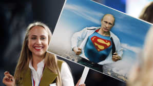 Nainen pitelee kylttiä jossa Putin repii paitansa ja alta paljastuu supermiespuku.